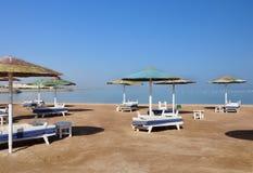 Sonnenschirme und Sonnenruhesessel auf dem Strand in Ägypten Lizenzfreies Stockbild