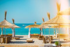 Sonnenschutz Regenschirme und deckchairs auf dem schönen Strand in Himara, Albanien stockbilder