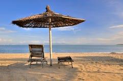 Sonnenschutz und Reststuhl auf Meersand Stockbilder