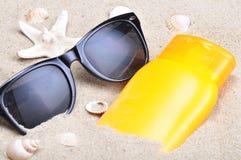 Sonnenschutz und Sonnenbrille auf einem Strand Lizenzfreie Stockbilder
