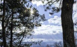 Sonnenstrahl, der durch Brüche mit weißen Wolken im Hintergrund überschreitet stockfoto