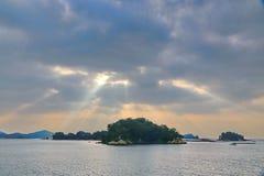 Sonnenstrahl, der durch dunkle Wolke über Inseln glänzt Stockfotografie