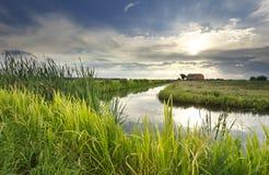 Sonnenstrahlen über Haus, Fluss und Wiese lizenzfreies stockbild