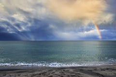 Sonnenstrahlen, die durch den Himmel bildet einen eindrucksvollen Regenbogen brechen Lizenzfreies Stockfoto