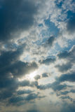 Sonnenstrahlen, die durch die Wolken auf blauem Himmel schlagen Stockbilder