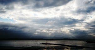 Sonnenstrahlen durch schwermütige Wolken über Wasserzeitversehen stock video