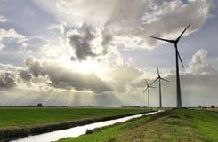 Sonnenstrahlen im stürmischen Himmel über Windkraftanlagen stockfotografie