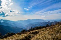 Sonnenstrahlen, Wolken und Berge Stockbild