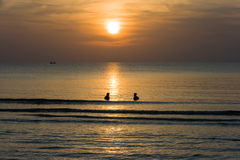 Sonnenuntergänge am Meer mit Schattenbildleuten im Wasser und in den Wolken und an der Welle im Ozean und im Boot Lizenzfreies Stockfoto