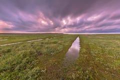 Sonnenuntergang über Abzugsgraben im Gezeiten- Sumpf Lizenzfreies Stockfoto