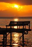 Sonnenuntergang über Bank auf Pier Stockfotos