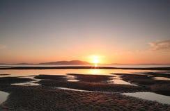 Sonnenuntergang über Berg am Strand Stockfotografie