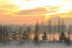 Sonnenuntergang über dem Dorf und der Winter nebeln ein Stockfotografie