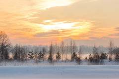 Sonnenuntergang über dem Dorf und der Winter nebeln ein Lizenzfreies Stockfoto