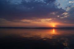 Sonnenuntergang über dem Fluss Die Sonne in den Wolken sitzt über dem Fluss stockfoto