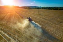 Sonnenuntergang über dem Mähdrescher, der an dem Feld arbeitet Lizenzfreie Stockfotografie
