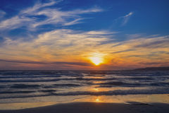 Sonnenuntergang über dem Meer auf dem Strand Stockfotos