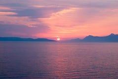 Sonnenuntergang über dem Meer mit dunstigen blauen und goldenen Farben Stockfotografie