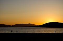 Sonnenuntergang über dem Meer mit Leuten Lizenzfreie Stockfotos