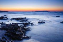 Sonnenuntergang über dem Meer und der Welle, die herauf den Strand sich waschen Stockfoto