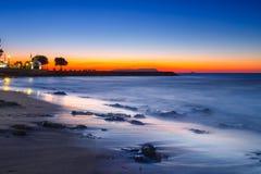 Sonnenuntergang über dem Meer und der Welle, die herauf den Strand sich waschen Stockfotografie