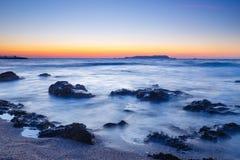 Sonnenuntergang über dem Meer und der Welle, die herauf den Strand sich waschen Lizenzfreies Stockbild
