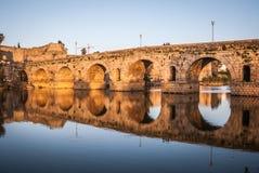 Sonnenuntergang über dem Monument, römische Brücke über dem Guadiana-Fluss in Mérida, Spanien Lizenzfreie Stockfotografie