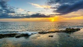 Sonnenuntergang über dem Pazifischen Ozean mit den Wellen, die auf Rocky Shoreline unter buntem Himmel zusammenstoßen Lizenzfreie Stockfotografie