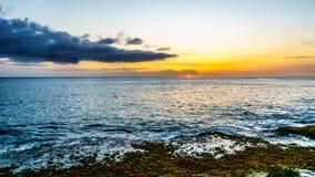 Sonnenuntergang über dem Pazifischen Ozean mit den Wellen, die auf Rocky Shoreline unter buntem Himmel zusammenstoßen Stockfoto