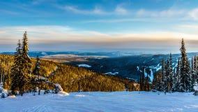 Sonnenuntergang über dem Schnee bedeckte Bäume in der Winterlandschaft vom hohen alpinen am Skiort von Sun-Spitzen lizenzfreie stockbilder