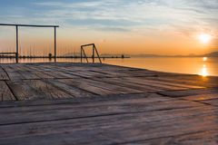 Sonnenuntergang über dem Wasser, dem Ponton und den Pfosten Lizenzfreie Stockbilder