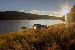 Sonnenuntergang über dem Zelt kampierte Seeufer Lizenzfreies Stockfoto