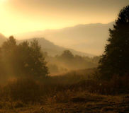 Sonnenuntergang über den nebeligen Bergen Lizenzfreie Stockfotos