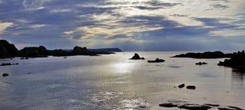 Sonnenuntergang über der Antrim-Küste, die Felseninseln, Balintoy silhouettiert Lizenzfreie Stockfotos