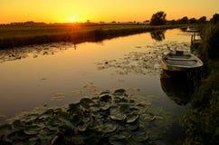 Sonnenuntergang über einem Abzugsgraben mit einem Boot und waterlily Lizenzfreies Stockbild