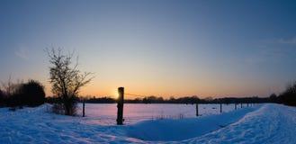 Sonnenuntergang über einem Feld im Schnee Lizenzfreie Stockfotos