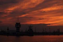 Sonnenuntergang über einem Industriehafen mit Kränen in Bulgarien, Varna Lizenzfreie Stockfotografie