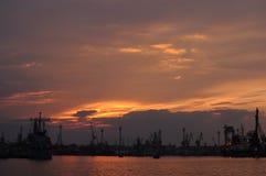 Sonnenuntergang über einem Industriehafen mit Kränen in Bulgarien, Varna Stockfotos