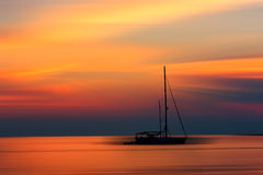 Sonnenuntergang über einem Meer mit einer einzelnen Yacht Lizenzfreie Stockfotos