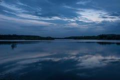 Sonnenuntergang über einem See-, Blauen und Orangehimmel lizenzfreies stockfoto