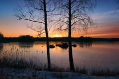 Sonnenuntergang über einem See im Winter Lizenzfreie Stockfotografie