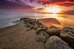 Sonnenuntergang über einem Strand mit großen Felsen Lizenzfreies Stockfoto