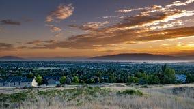 Sonnenuntergang über einer Stadt in einem Tal mit Bergen und einem großen See im Abstand stockfotografie