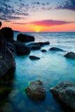 Sonnenuntergang über felsiger Küstenlinie Lizenzfreies Stockfoto