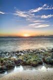 Sonnenuntergang über felsiger Küstenlinie Stockfotos