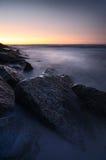 Sonnenuntergang über felsiger Küstenlinie Stockbild