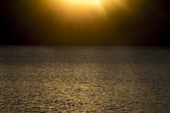 Sonnenuntergang über gewelltem Wasser stockfotos
