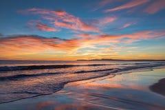 Sonnenuntergang über Küste mit gesättigten Farben im Himmel und Reflexionen im Wasser stockbilder