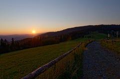 Sonnenuntergang über Landstraße und bewaldeten Hügeln Polnische Berge Strahlen der Sonne fallend auf einen ländlichen Zaun Stockfoto