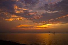 Sonnenuntergang über Meer mit schwermütigem Himmel, dunkle Sturmwolken Stockbilder